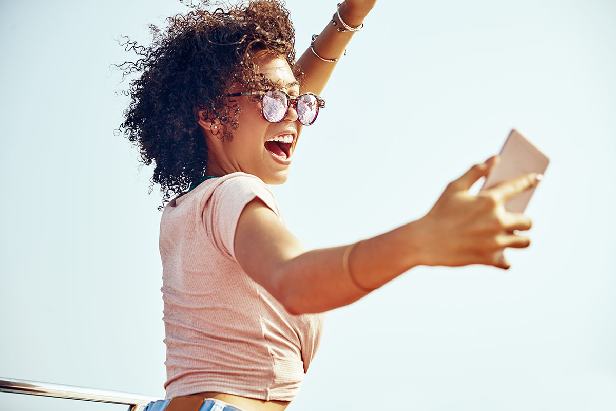 Carefree young woman wearing sunglasses and laughing while standing on a boat against a blue sky taking selfies during summer vacation