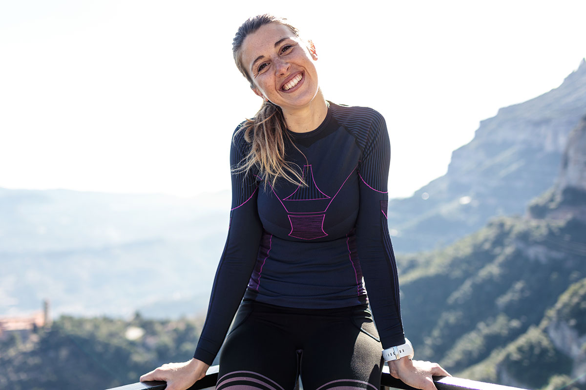 Portrait of sporty young woman looking at the camera on the mountain peak.
